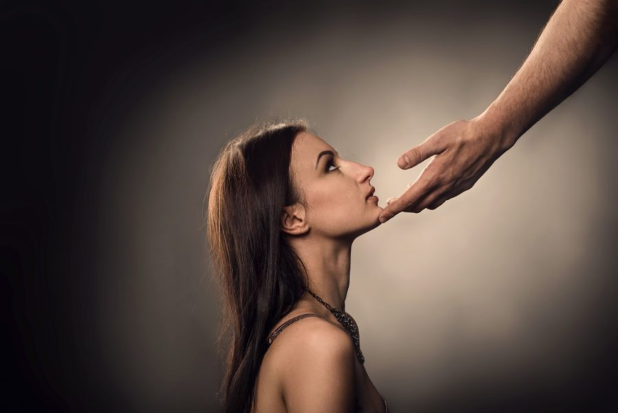 Male hand touches to woman face as Sexual Harassment