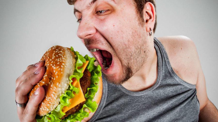 мужчина ест фаст фуд