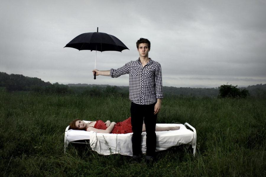 мужчина держит зонт над женщиной