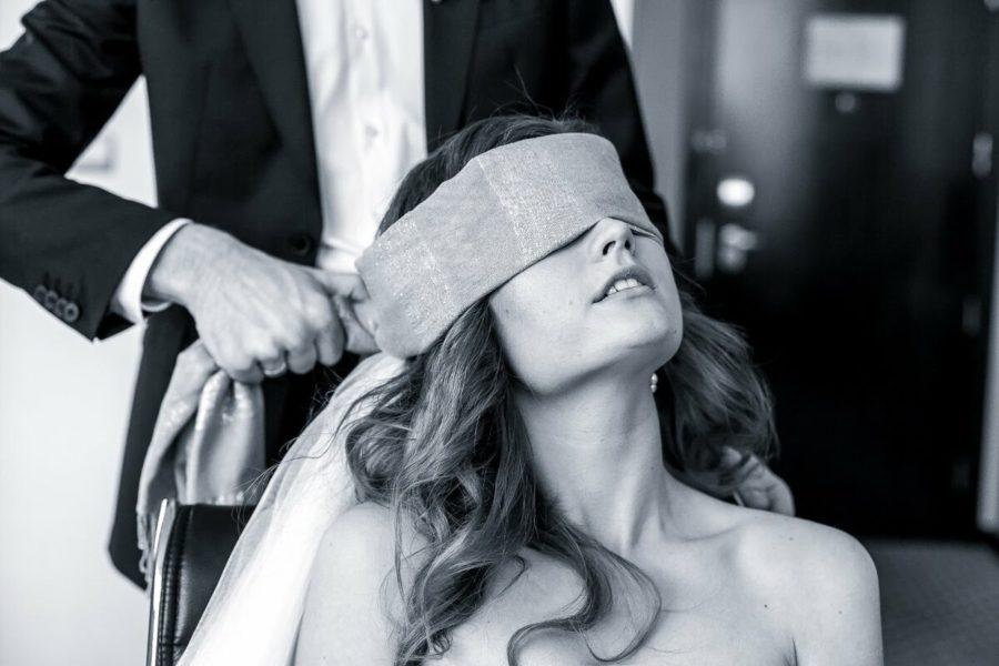 мужчина завязывает девушке глаза