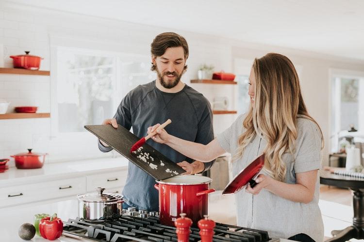 парень с девушкой готовят вместе еду