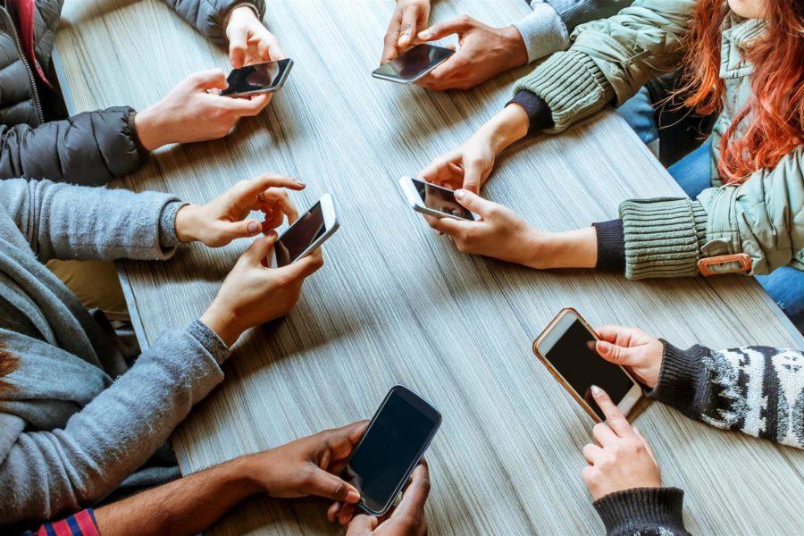 руки держат телефоны