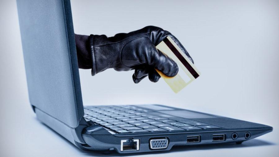 ноутбук с рукой и кредиткой