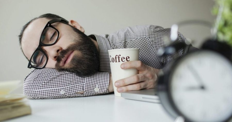 Парень лежит на столе с кружкой кофе