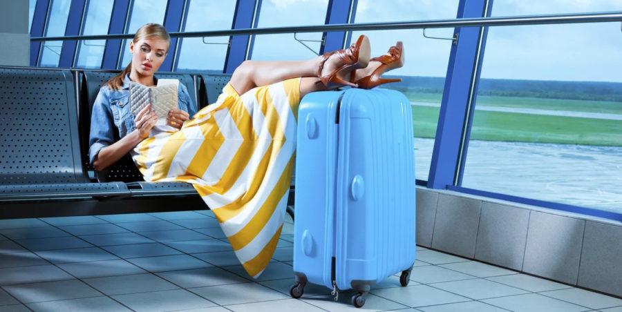 Девушка в аэропорту с  чемоданом