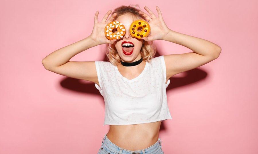 Девушка улыбается с пончиками