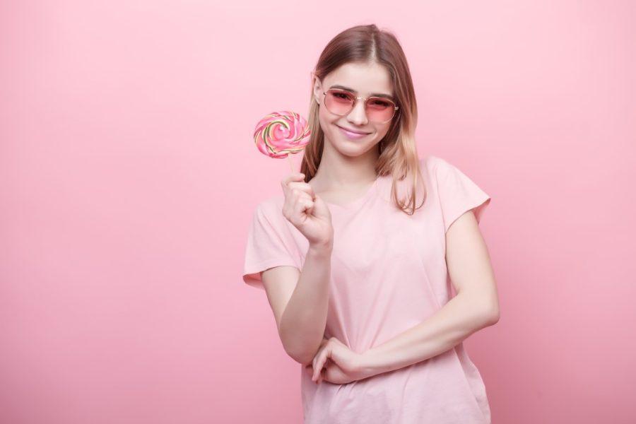 девушка с леденцом на розовом фоне