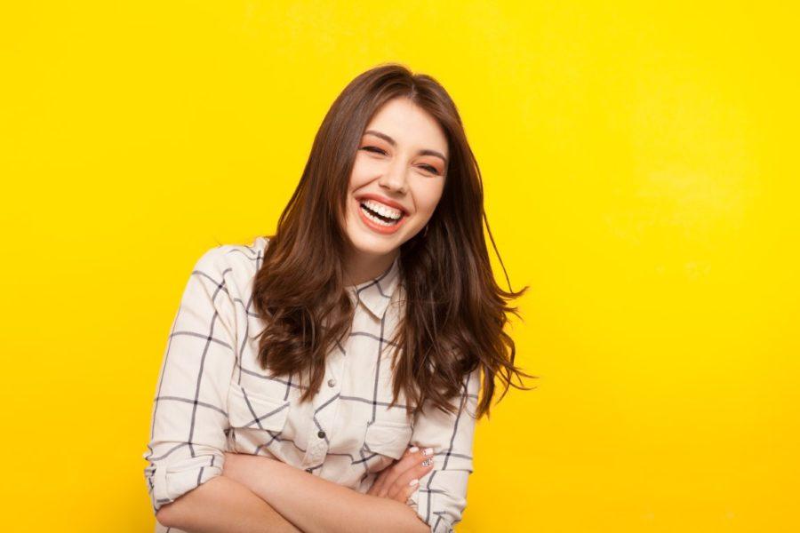 девушка на желтом фоне смеется