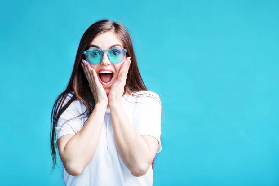 девушка в голубых очках радуется