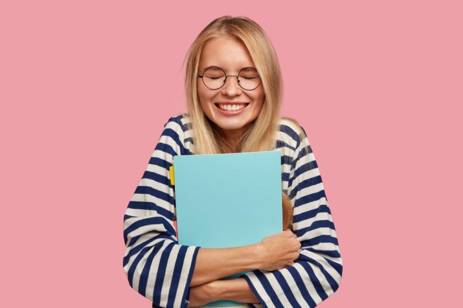 счастливая девушка держит тетрадь