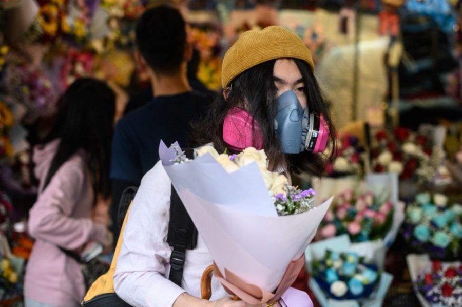 парень в гонконге с цветами и маске