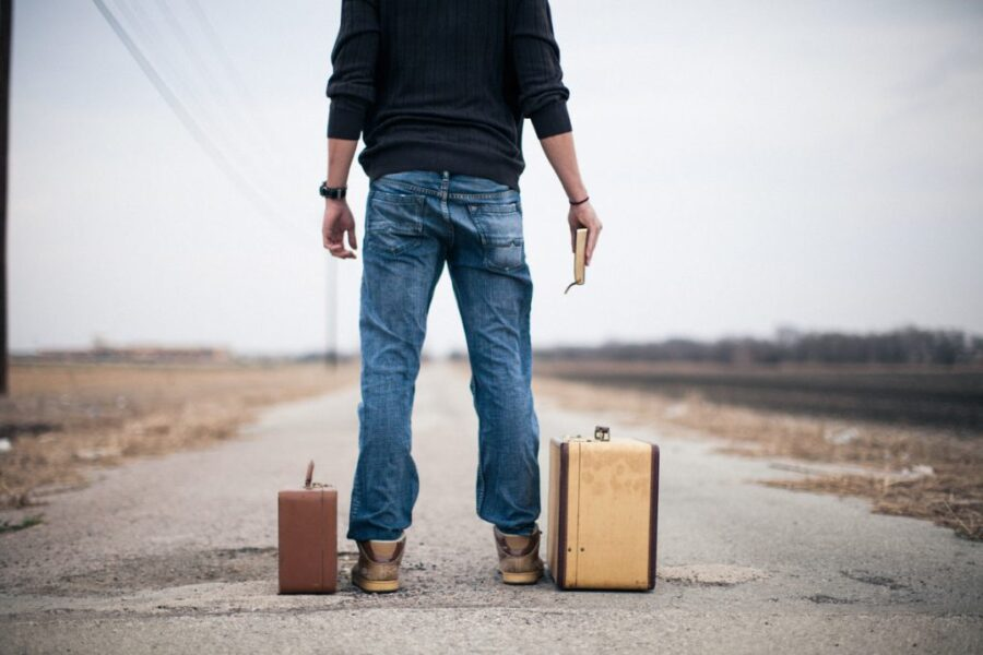 парень на дороге с чемоданами