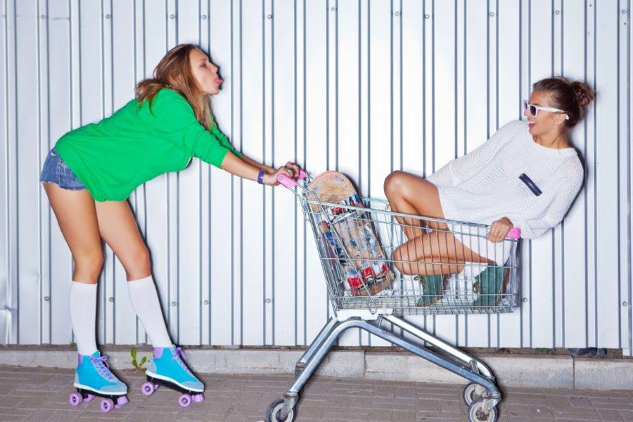 девушки катаются на коляске для продуктов
