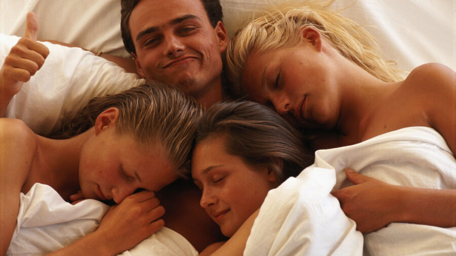 парень и две девушки в кровати