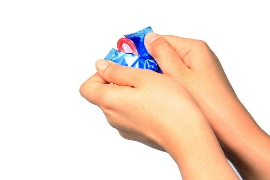девушка достает презерватив из упаковки 2