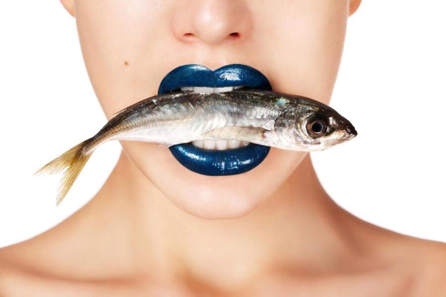 девушка держит рыбу в зубах