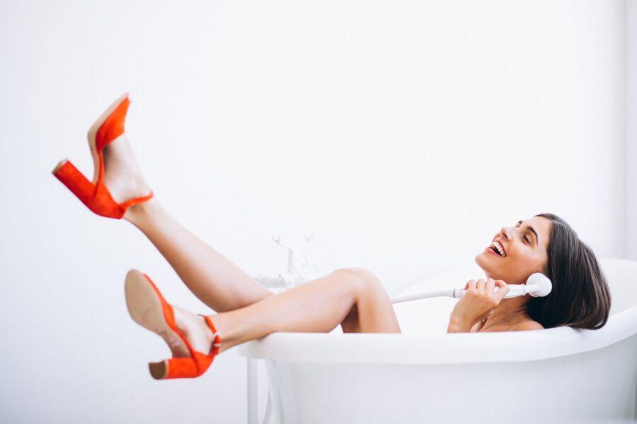 девушка в ванной говорит по телефону