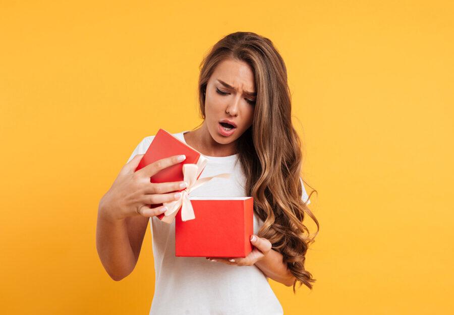 девушка удивленная смотрит в коробку