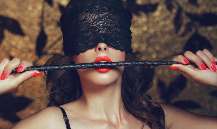женщина держит плеть во рту