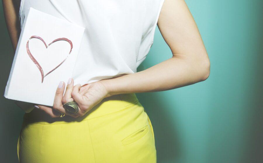 девушка с открыткой за спиной