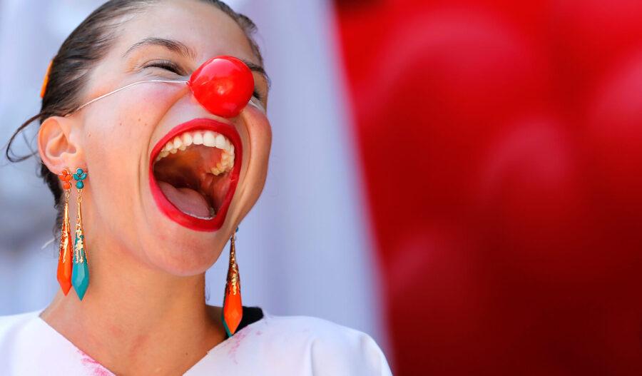 девушка с красным носом смеется