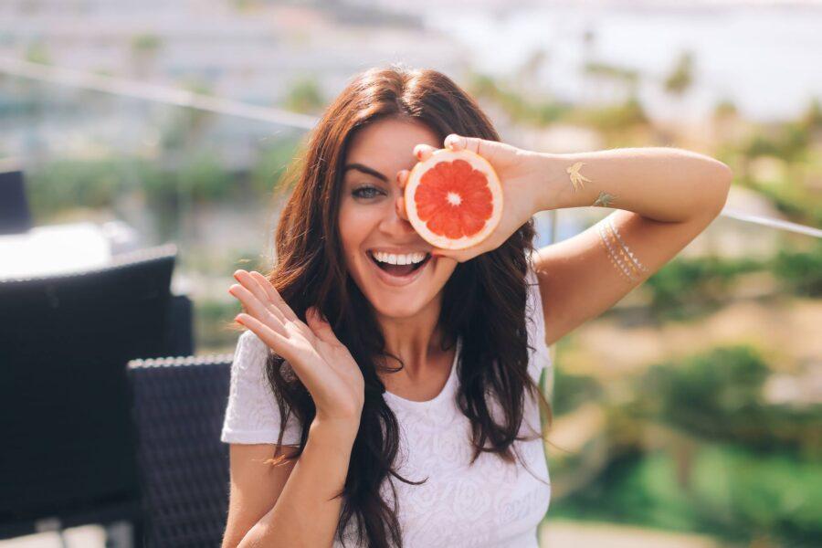 девушка улыбается с грейпфрутом