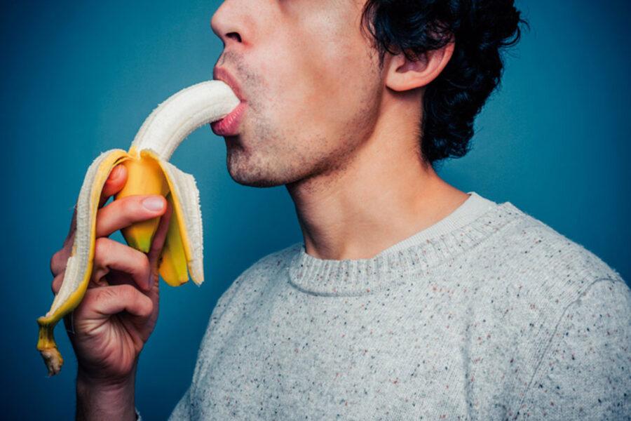 мужчина сосет банан