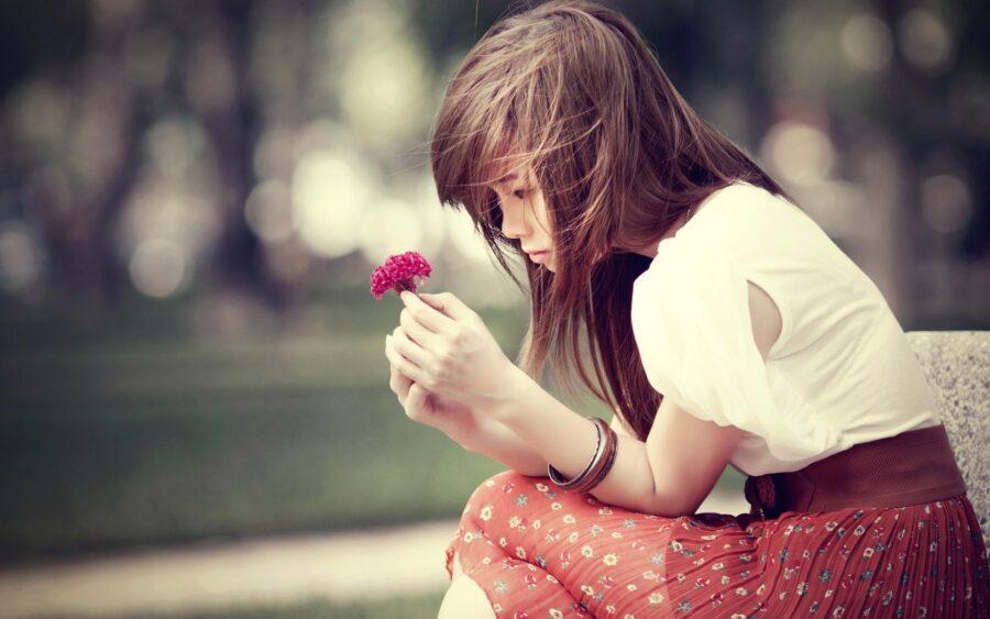 девушка с цветочком задумалась