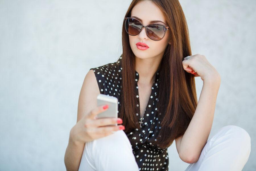 брюнетка смотрит в телефон