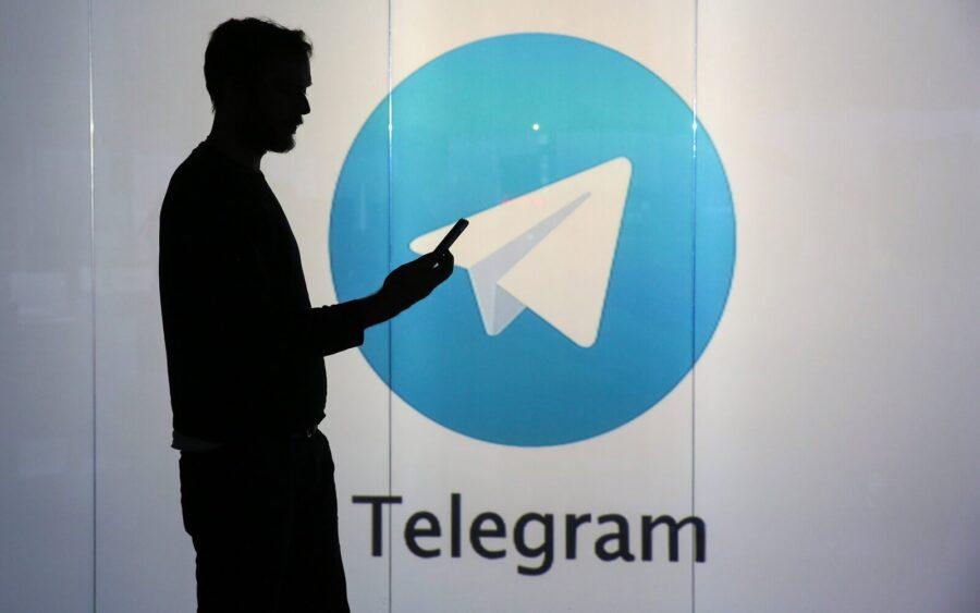 силуэт парня на фоне знака Телеграмм