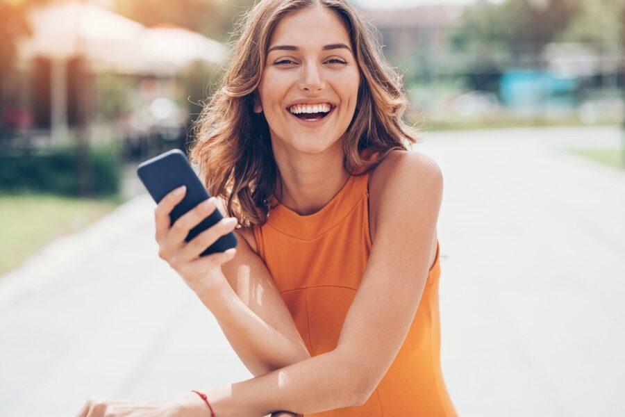 девушка улыбается с телефоном