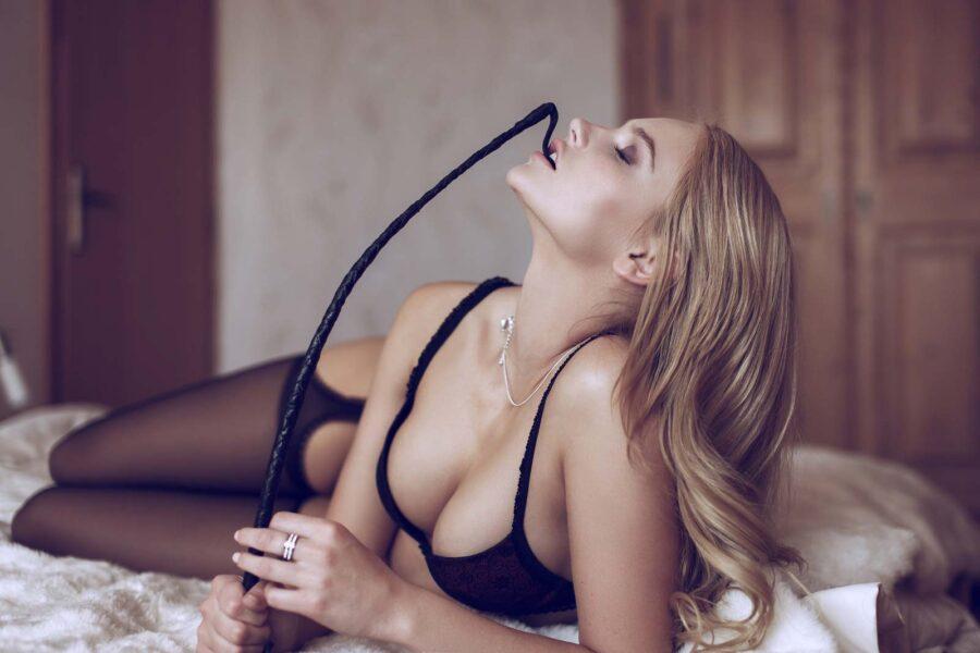 девушка держит плеть во рту