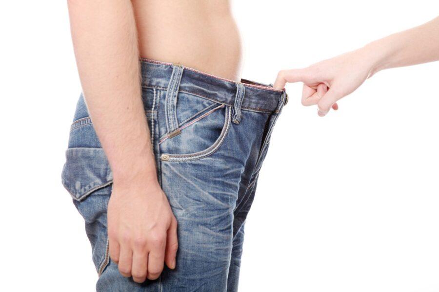 рука девушки оттягивает джинсы парня