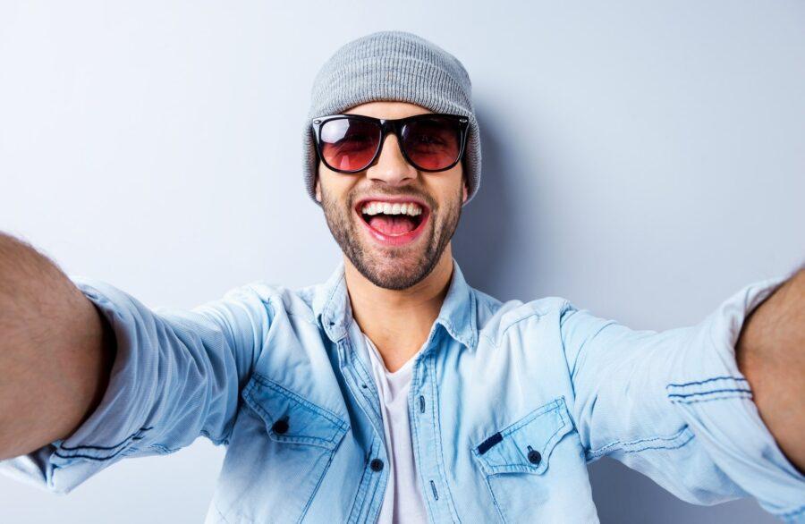 парень в очках смеется