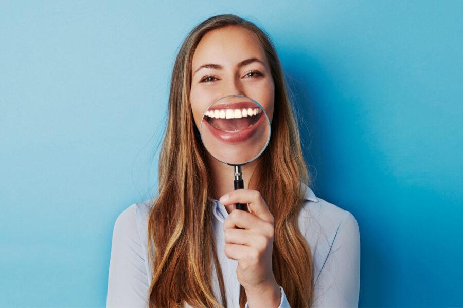 девушка улыбается с лупой