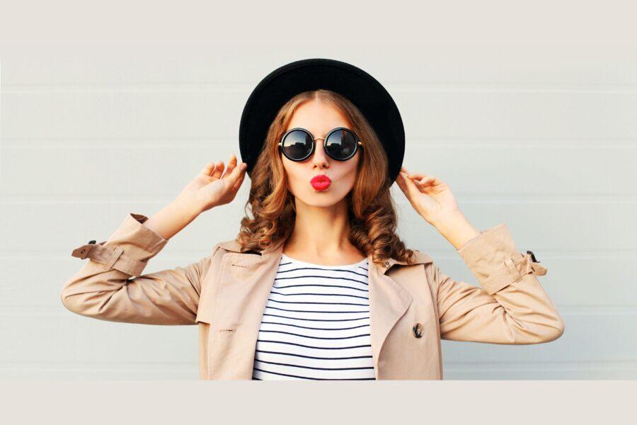 девушка держится за шляпку
