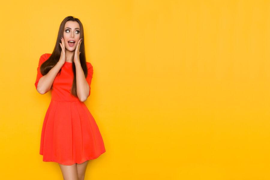 брюнетка в красном платье удивлена