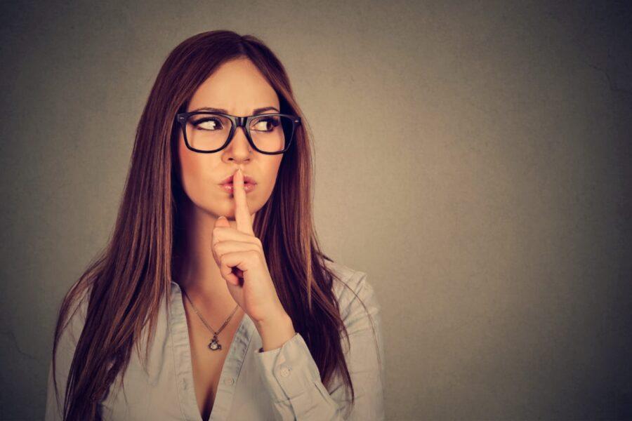 девушка с пальцем у губ