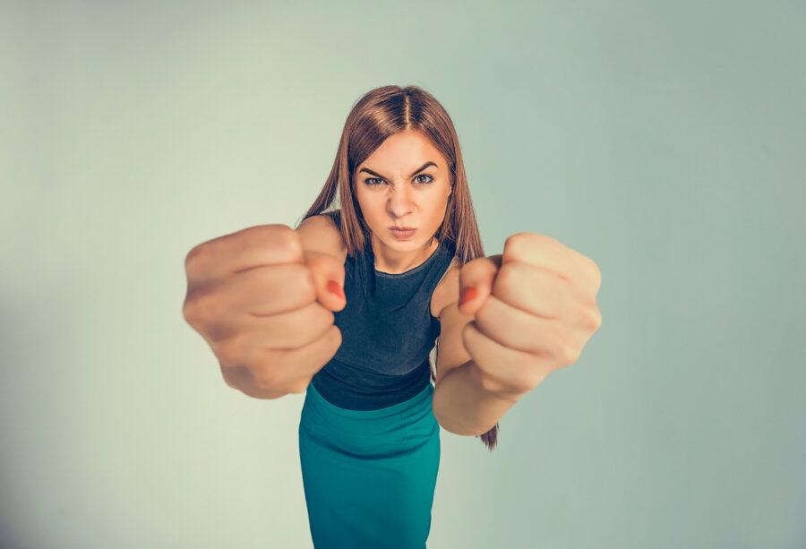 девушка показывает кулаки