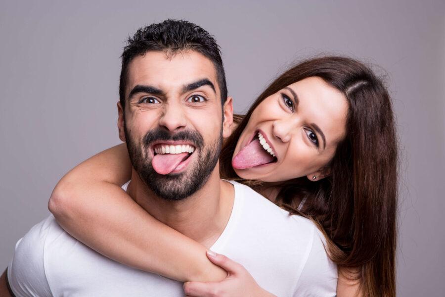 девушка и парень показывают язык