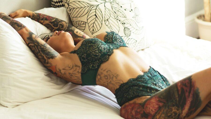 девушка в татуировках на кровати