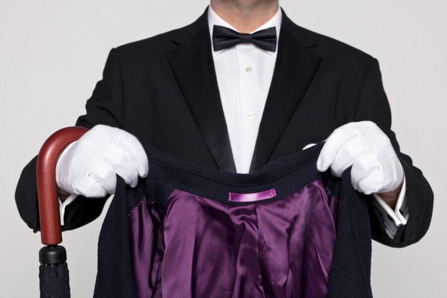 дворецкий держит одежду