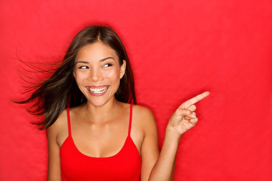 радостная девушка показывает пальцем