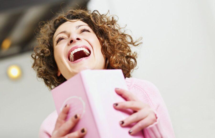 девушка с блокнотом смеется