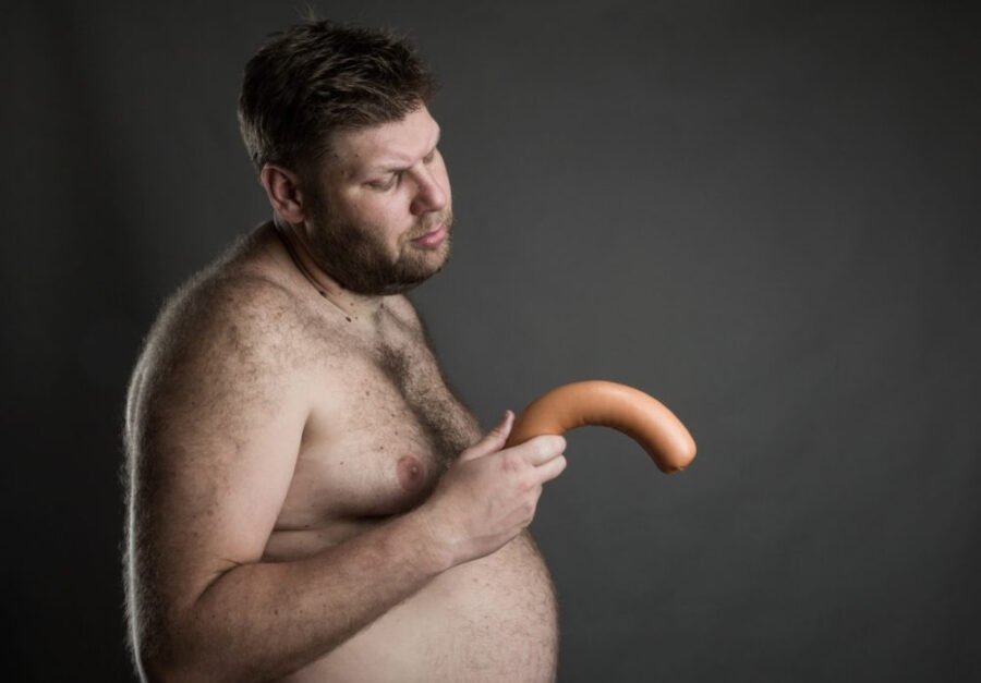 мужчина держит сосиску