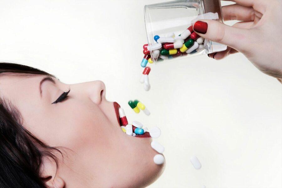 девушка глотает таблетки