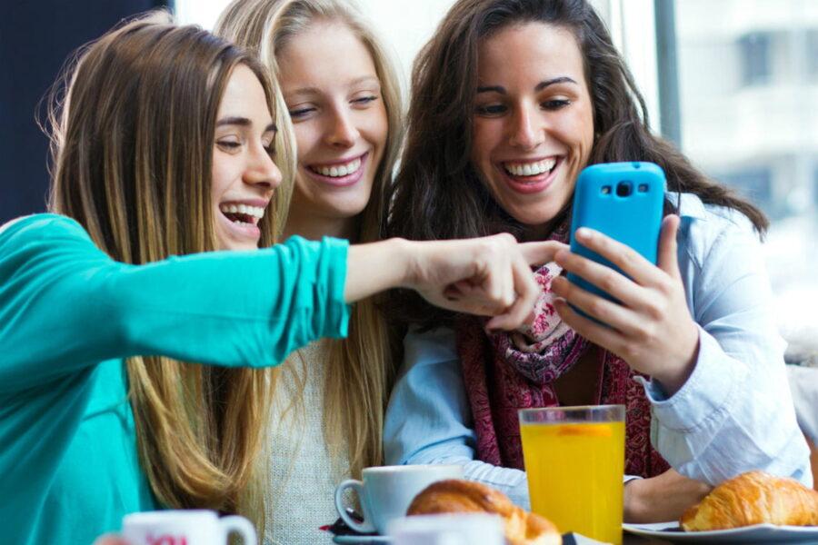 подруги смеются с телефоном