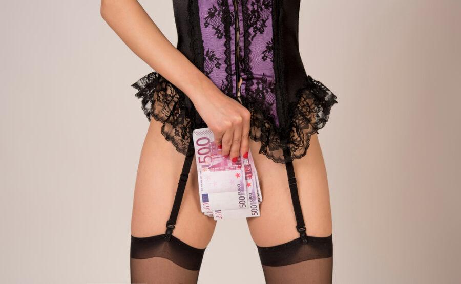 девушка прикрывается долларами