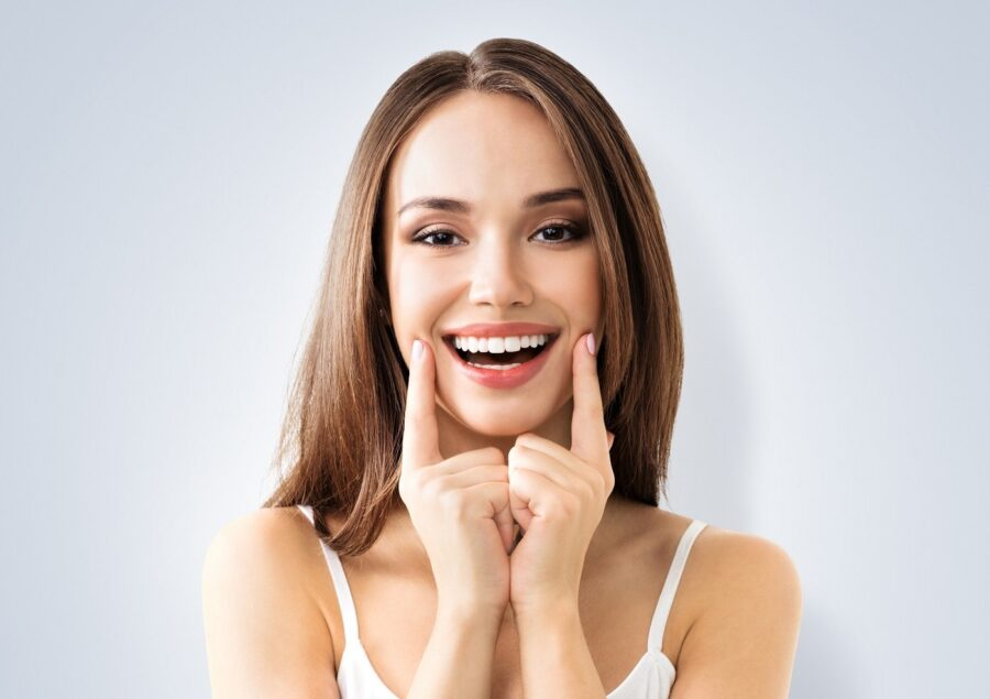 девушка показывает улыбку