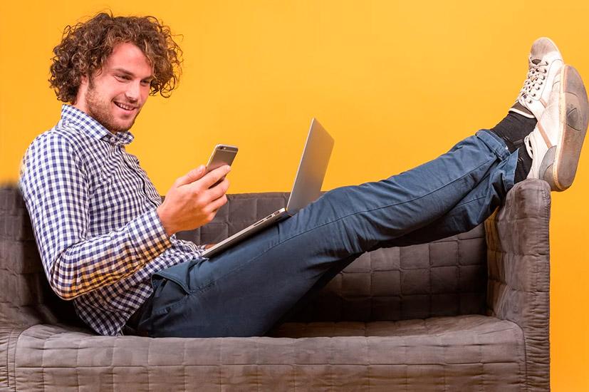 парень с ноутбуком и телефоном